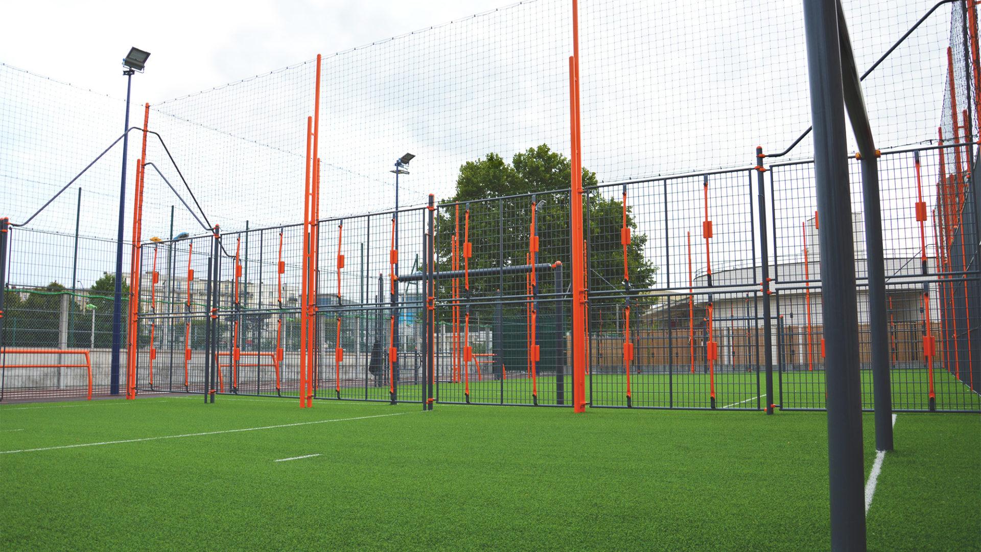 Terrain multisport sur gazon synthétique sablé avec filet pare-ballon et lignes de jeu à Drancy
